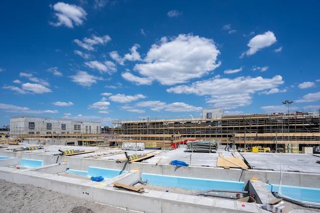 Foto horizontal de um canteiro de obras com andaimes sob um céu azul claro