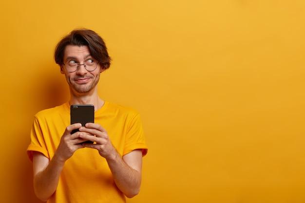 Foto horizontal de um cara alegre e moderno segura o smartphone e envia fotos engraçadas de uma festa para um amigo, digita e navega na rede, vestido casualmente, posa contra a parede amarela, copie o espaço