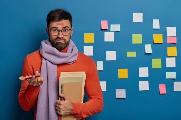 Foto horizontal de um cara barbudo hesitante dando de ombros, vestido com roupas quentes da moda, segurando um diário em espiral e blocos de notas