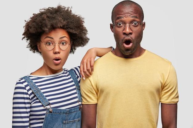 Foto horizontal de um casal de família de pele escura e emotivo que não espera receber contas, fica de queixo caído, não vê como sair, não tem dinheiro para pagar, isolado sobre uma parede branca. conceito omg