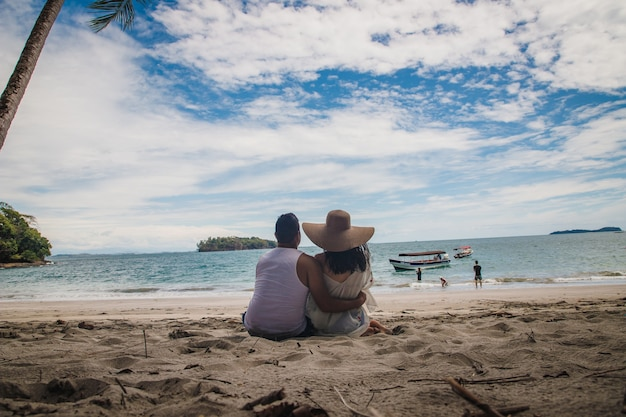 Foto horizontal de um casal sentado em uma praia em direção às calmas águas azuis sob o lindo céu