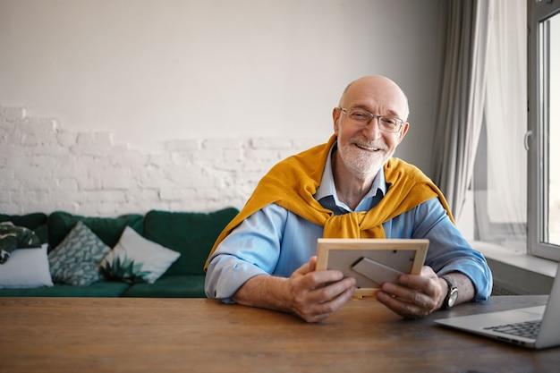Foto horizontal de um empresário elegante de 60 anos de idade, usando óculos retangulares, sentado em frente a um computador portátil aberto, segurando um retrato de família em uma moldura e sorrindo alegremente