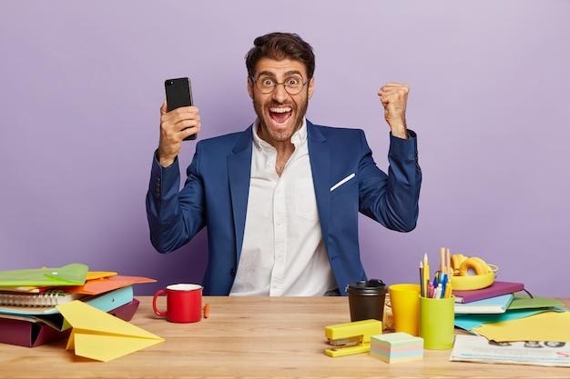Foto horizontal de um empresário triunfante e radiante, sentado à mesa do escritório