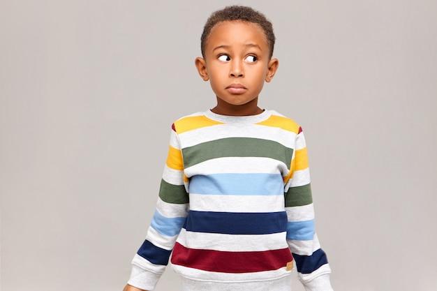 Foto horizontal de um garoto afro-americano confuso e engraçado em um suéter listrado desviando o olhar com uma expressão facial sem noção, sentindo-se culpado por comer todos os doces, fingindo ser inocente. eu não sei
