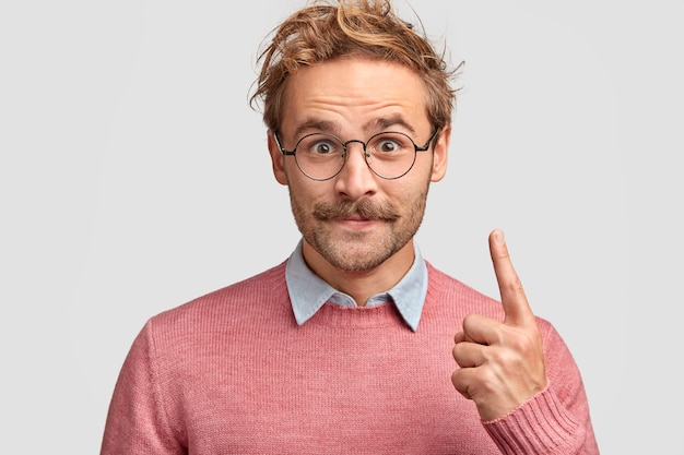 Foto horizontal de um hipster bonito e satisfeito com bigode, vestido com roupas elegantes