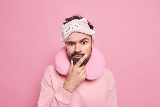 Foto horizontal de um homem adulto barbudo sério com expressão rígida, usando um travesseiro de viagem confortável e uma máscara de dormir vestida casualmente