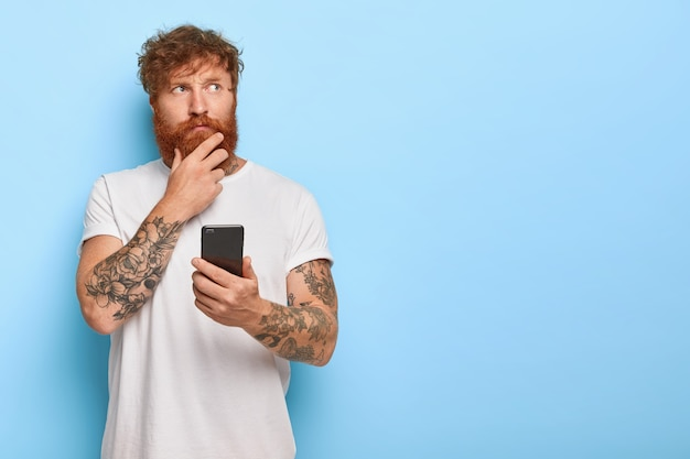 Foto horizontal de um homem adulto contemplativo sério tocando uma espessa barba ruiva, segurando o telefone celular, acessando o feed de notícias online, pensa nas notícias recentes, tem braços tatuados, usa uma camiseta branca casual