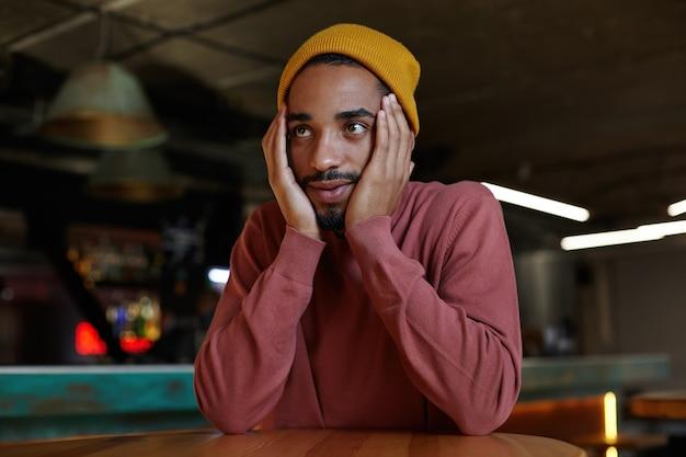 Foto horizontal de um homem atraente barbudo, de olhos castanhos e pele escura, mantendo as mãos na mesa e inclinando a cabeça sobre ela, sentado no interior do café da cidade e esperando seu café