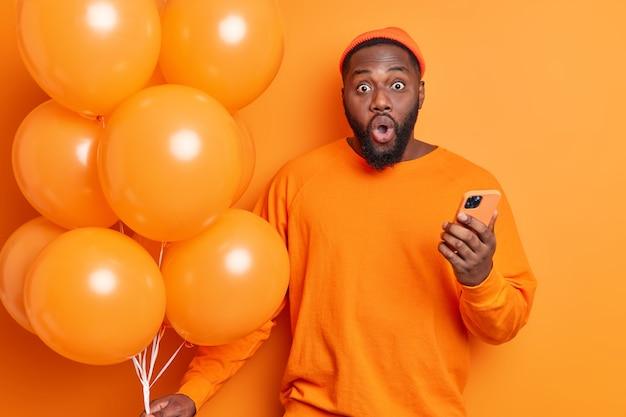 Foto horizontal de um homem barbudo chocado olhando surpreendentemente para a câmera, vestido casualmente, segurando um celular e um monte de balões em uma festa isolado sobre uma parede laranja