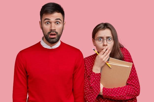 Foto horizontal de um homem barbudo intrigado com um suéter vermelho, namorada assustada com lápis e bloco de notas em espiral