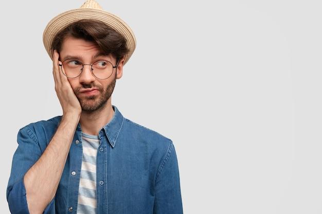 Foto horizontal de um homem barbudo intrigado e pensativo segurando a bochecha