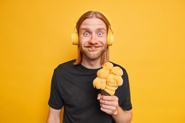Foto horizontal de um homem barbudo positivo com longos cabelos ruivos no rosto manchado de sorvete segura um grande sorvete amarelo vestido casualmente e se diverte curtindo as férias de verão ouve música com fones de ouvido
