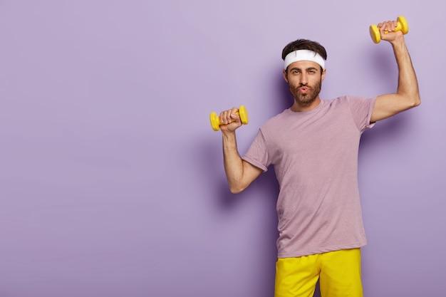 Foto horizontal de um homem bonito com a barba por fazer malhando na academia, treina bíceps com o instrutor esportivo, usa roupa ativa, bandana branca