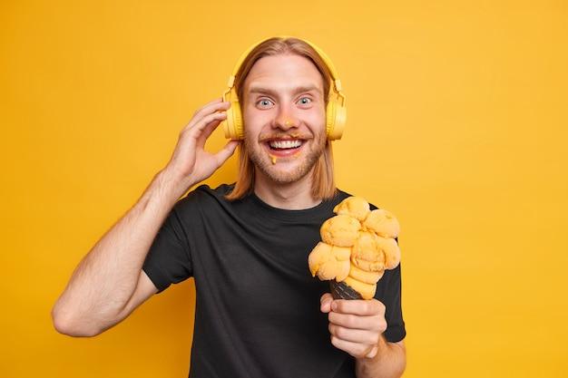 Foto horizontal de um homem bonito e alegre com longos cabelos ruivos, barba manchada no rosto enquanto toma um delicioso sorvete ouve a faixa de áudio favorita no rádio usa fones de ouvido sem fio de parede amarela