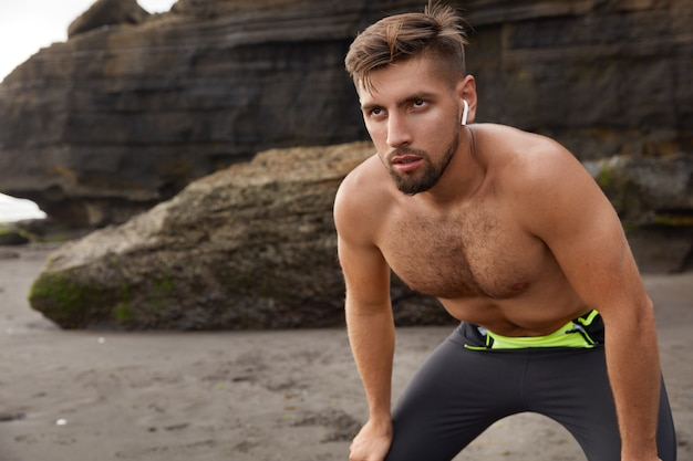Foto horizontal de um homem bonito e determinado desportivo inclinado sobre os joelhos