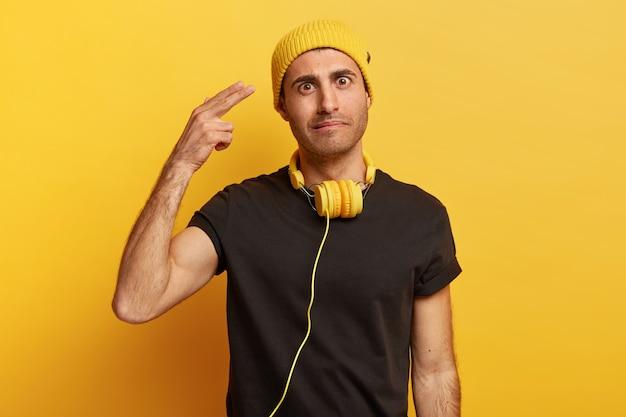 Foto horizontal de um homem branco com cabelo escuro, atirando na têmpora, demonstra um gesto suicida