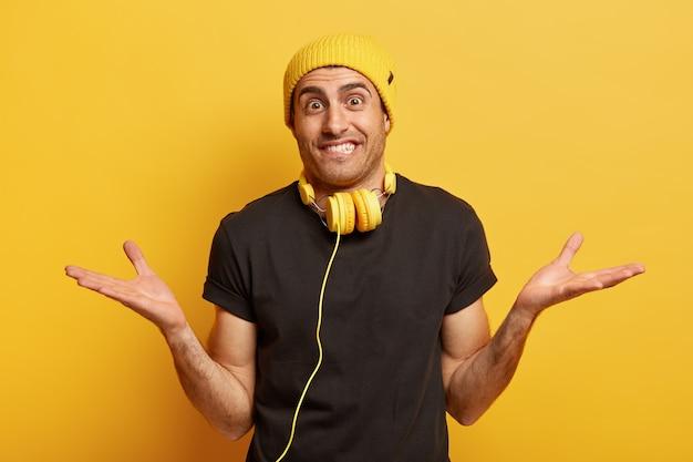 Foto horizontal de um homem branco otimista com as mãos em lados diferentes