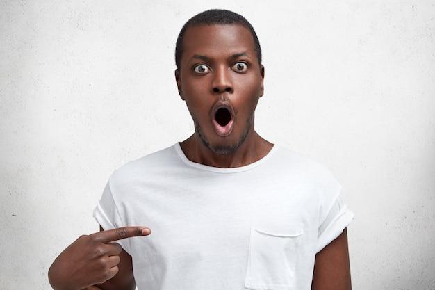 Foto horizontal de um homem de pele escura chocado e surpreso com uma expressão inesperada, olhares com o queixo caído e os olhos arregalados