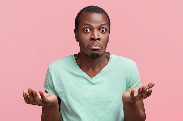 Foto horizontal de um homem de pele escura, hesitante e bonito, encolhendo os ombros, sendo incerto e inseguro, curva o lábio inferior e olha fixamente, posa contra rosa