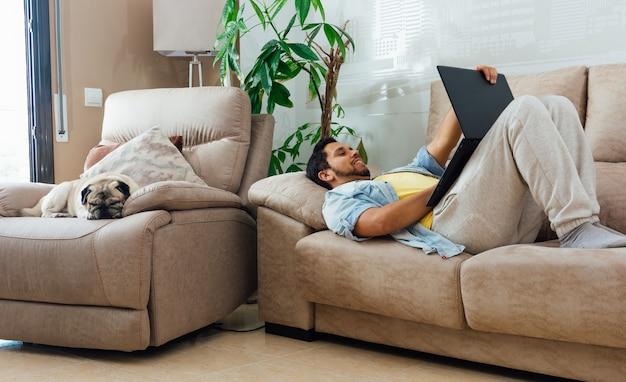 Foto horizontal de um homem deitado no sofá em casa e trabalhando com um laptop preto