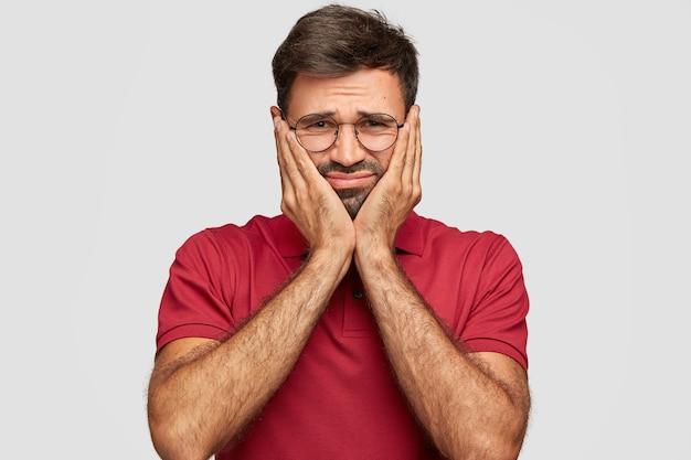 Foto horizontal de um homem descontente com cabelo escuro, tocando as bochechas com as mãos, tem expressão facial negativa, usa uma camiseta casual vermelha, fica de pé contra uma parede branca. conceito de pessoas e emoções
