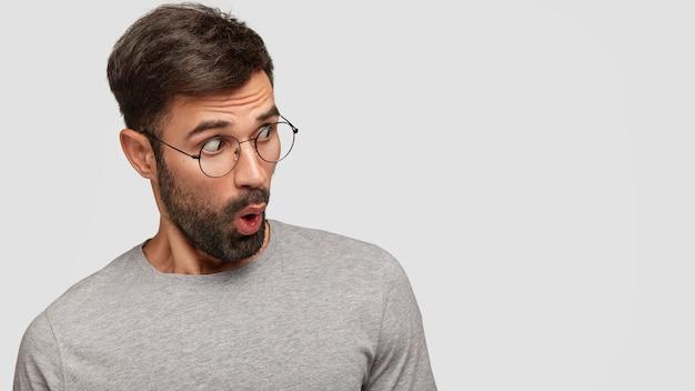 Foto horizontal de um homem estupefato com o queixo caído, percebe algo surpreendente, olha de lado, vestido com uma camisa cinza casual, isolado sobre uma parede branca