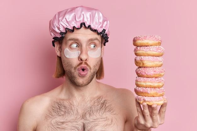 Foto horizontal de um homem europeu atordoado aplicando compressas hidratantes sob os olhos mantendo a boca aberta, olhando para uma pilha de deliciosas poses de donuts com os ombros nus contra a parede rosa do estúdio