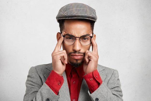 Foto horizontal de um homem mestiço pensativo, vestido formalmente, mantendo os dedos nas têmporas,