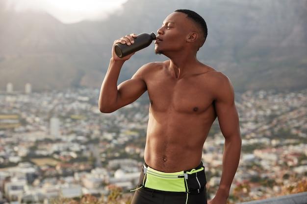 Foto horizontal de um homem negro com corpo esportivo, hidrata-se com água, segura a garrafa, sente sede após o treino cardiovascular, respira por causa de um ataque cardíaco, sente-se desidratado, se opõe à paisagem de montanha