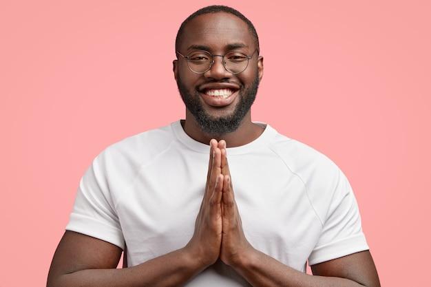 Foto horizontal de um homem negro sorridente com as mãos juntas, acredita em algo positivo