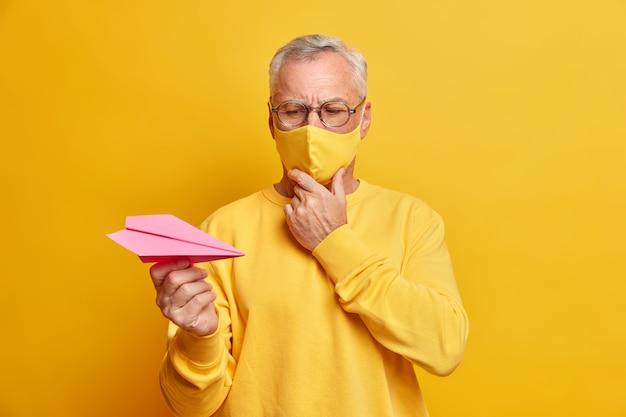 Foto horizontal de um homem pensativo aposentado de óculos olhando atentamente para o avião de papel, pensando seriamente em como superar a doença usa máscara protetora durante poses de quarentena em ambientes fechados