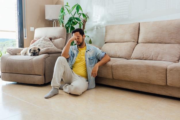 Foto horizontal de um homem sentado no chão em casa com uma expressão cansada