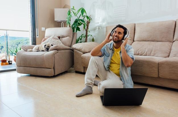 Foto horizontal de um homem sentado no chão em frente a um laptop ouvindo música