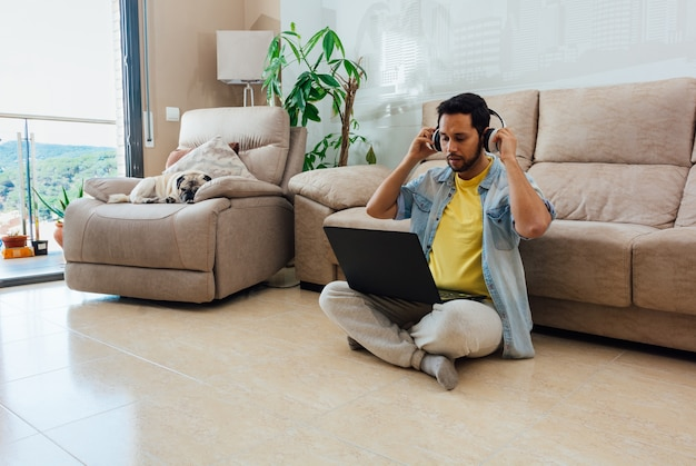 Foto horizontal de um homem sentado no chão, ouvindo música e trabalhando com o laptop em casa