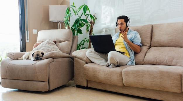 Foto horizontal de um homem sentado no sofá, trabalhando com um laptop e se sentindo chocado