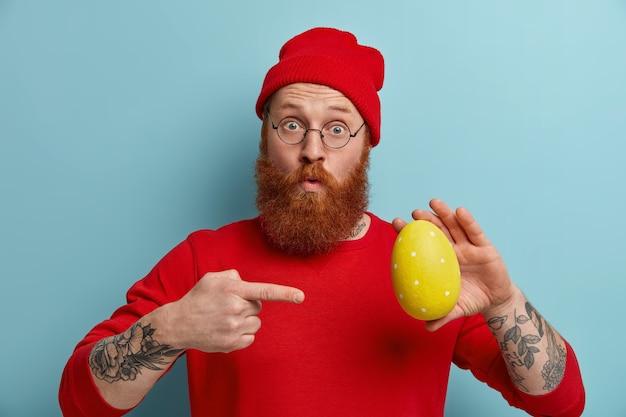Foto horizontal de um homem surpreso com uma espessa barba ruiva, aponta para um grande ovo de páscoa amarelo decorado, demonstra sua habilidade de desenhar e decorar, parece maravilhado. pessoas, feriado