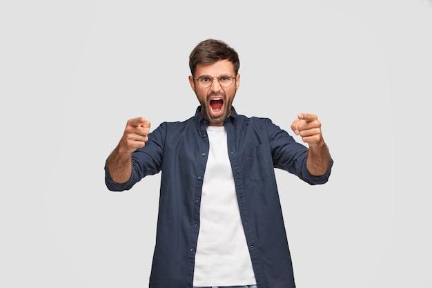 Foto horizontal de um homem zangado e furioso com uma expressão irritada, gritando com alguém, apontando com os dois dedos indicadores para a câmera
