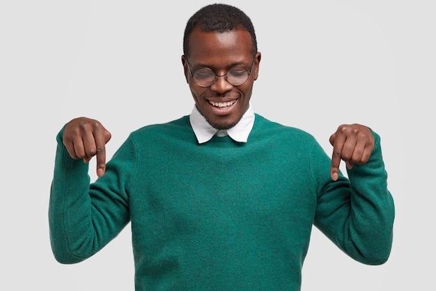 Foto horizontal de um jovem afro-americano positivo apontando ambos os dedos indicadores para baixo, com a certeza de sua escolha, com um sorriso dentuço