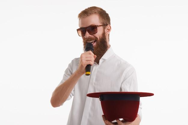 Foto horizontal de um jovem artista de rua elegante, alegre, com uma barba ruiva difusa, falando no microfone sem fio e estendendo a mão segurando o chapéu, pedindo dinheiro usando óculos escuros