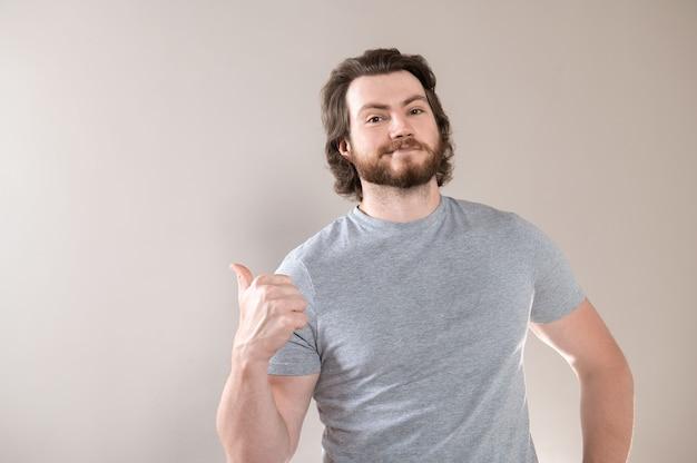 Foto horizontal de um jovem barbudo feliz vestido com uma camiseta, indica com o polegar ao lado, isolado no fundo cinza do estúdio