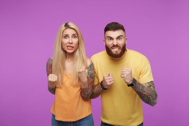 Foto horizontal de um jovem casal tatuado e animado dobrando os punhos com as mãos levantadas e mostrando os dentes enquanto faziam caretas, em pé sobre um fundo roxo
