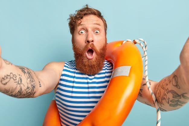 Foto horizontal de um jovem chocado com uma boia salva-vidas.
