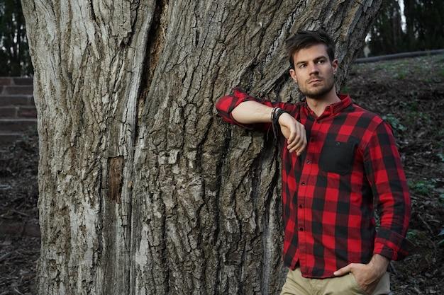 Foto horizontal de um jovem encantador apoiado em uma árvore velha e grossa com a mão