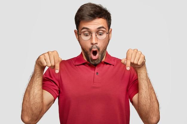 Foto horizontal de um jovem estupefato parece surpreendentemente e indica para baixo, sendo atordoado por algo inacreditável, usa uma camiseta vermelha brilhante casual, fica contra uma parede branca