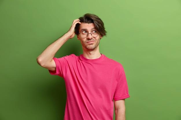 Foto horizontal de um jovem europeu pensativo e bonito coçando a cabeça parece duvidosamente de lado