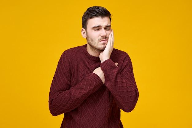 Foto horizontal de um jovem feliz e frustrado em um macacão de malha com problemas de cárie dentária, precisa ir ao dentista, mantendo a mão em sua bochecha e fazendo uma careta.
