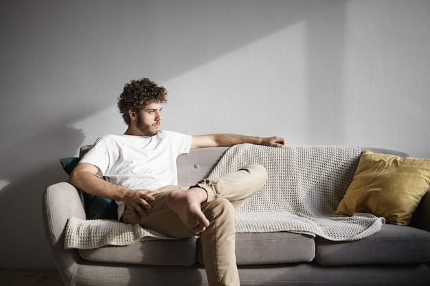 Foto horizontal de um jovem solteirão de trinta anos, caucasiano, na moda, com cabelos ondulados e barba espessa, sentado confortavelmente no sofá da sala de estar, olhando sério, tentando relaxar depois do trabalho
