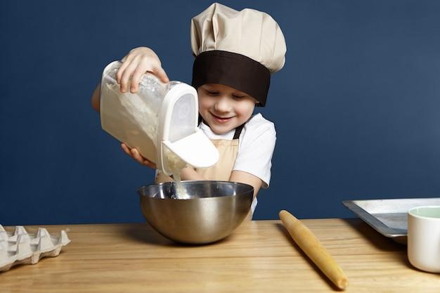 Foto horizontal de um menino europeu feliz de 8 anos com uma expressão animada enquanto derrama farinha de trigo em uma tigela de metal enquanto vai fazer um doce sozinho, de pé na parede em branco da cozinha