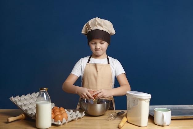 Foto horizontal de um menino sério usando avental bege e chapéu quebrando um ovo em uma tigela de metal