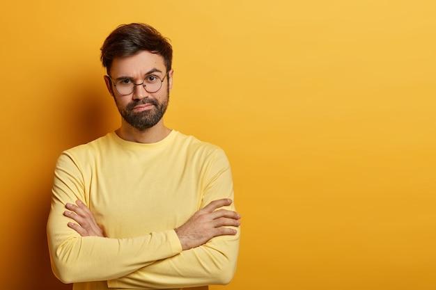 Foto horizontal de um modelo masculino sério com os braços cruzados, não gosta de fazer compras, fica entediado de passar o tempo com a compra da esposa, usa óculos e macacão, isolado sobre a parede amarela